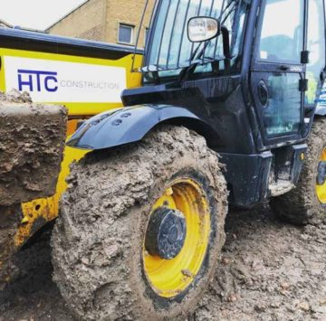HTC Construction sticker on a muddy jcb